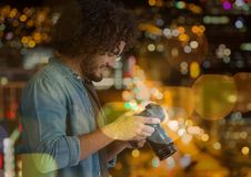 photographer looking to the photos on camera, in the city at night (with blurred lights) Royalty Free Stock Photography