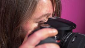 Photographer looking through viewfinder of camera