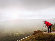 Photographer looking into viewfinder of dslr digital camera stand on tripod. Artist  photographing mountain and cloudy landscape. Man check picture on screen Royalty Free Stock Images