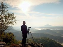 Photographer looks into the landscape and listen the silence. Man prepare camera to takes photos. Photographer looks into the landscape and listen the silence Stock Photos