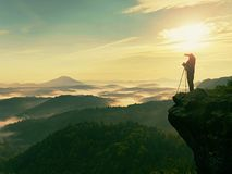 Photographer looks into the landscape and listen the silence. Man prepare camera to takes photos. Photographer looks into the landscape and listen the silence Royalty Free Stock Photo