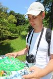 Photographer looks on map in sochi arboretum Royalty Free Stock Photography