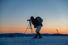 Photographer makes sunset/sunrise photo. Photographer with help of tripod are making landscape shot in sunset / sunrise time. Situation in mountains. Snow in Stock Photos