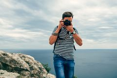 Photographer male tourist with a professional digital camera and lens. Photographs on the edge of the mountains to the sea face forward Royalty Free Stock Image