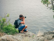 Photographer tourist taking pictures sitting on the seascape. Photographer male tourist taking pictures sitting on the edge of a cliff seascape Stock Photos