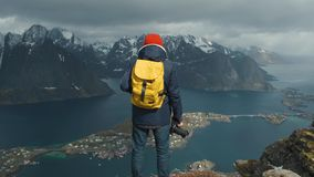 Photographer male with a yellow backpack, stands on the top of the mountain nature. adventure travel concept. Norway. Lofoten Reine stock footage