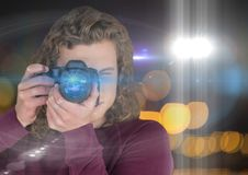 Photographer man with long hair taking a photo (foreground). Blurred lights and flares behind and ov Stock Photo