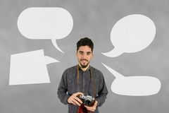 Photographer man with speech bubbles against grey background Royalty Free Stock Photography
