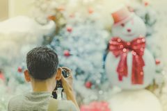 Photographer man take photo of decorated Christmas tree and a sn royalty free stock photography