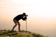 Photographer. Man photographer on the top of the mountain taking nature and landscape pictures Stock Photography