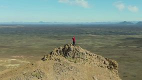 Photographer Man Traveler on Mountain Top. Iceland. Aerial View. Photographer Man Traveler on Mountain Top Taking Pictures in Hverir Area on Sunny Day. Iceland stock video