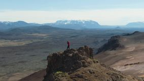 Photographer Man Traveler on Mountain Top Taking Pictures. Iceland. Aerial View. Photographer Man Traveler on Mountain Top Taking Pictures in Hverir Geothermal stock footage