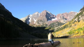 Photographer at Maroon Bells. A photographer capturing the maroon bells and fall aspens near aspen colorado reflected in maroon lake stock video
