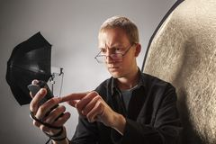 Photographer measures the light in the studio Royalty Free Stock Image