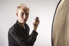 Photographer measures the light in the studio Royalty Free Stock Photos