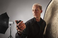 Photographer measures the light in the studio Stock Photography