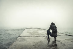 Photographer on a misty pier. Royalty Free Stock Images