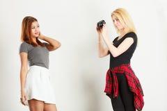 Blonde girl photographing mulatto woman Stock Image