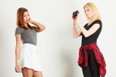 Blonde girl photographing mulatto woman. Photographer and model. Blonde girl shooting images, taking photos with camera, photographing mulatto female model Royalty Free Stock Image