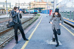 Photographer and a model in a pose on a railway station Royalty Free Stock Photo