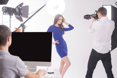 Photographer and model at studio. Young men photographing model at studio Stock Photos