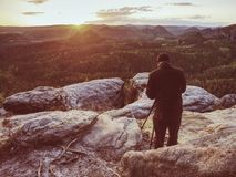 Photographer on mountain cliff take picture of landscape awaking. Photographer on a mountain cliff taking picture of landscape awaking.   Dreamy fogy landscape stock images