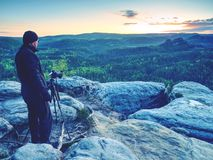 Photographer on mountain cliff take picture of landscape awaking. Photographer on a mountain cliff taking picture of landscape awaking.   Dreamy fogy landscape stock photography