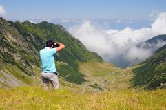 Photographer on mountain top Royalty Free Stock Image
