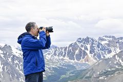 Photographer in mountains. Male photographer taking pictures in Canadian Rocky Mountains in Jasper National Park Stock Photos