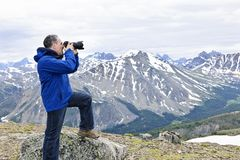 Photographer in mountains. Male photographer taking pictures in Canadian Rocky Mountains in Jasper National Park Stock Image