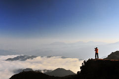 Photographer in mountains. Male photographer taking sea of clouds pictures in china Minya Konka Mountains in Tibetan Plateau Stock Images