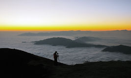 Photographer in mountains. Male photographer taking sea of clouds pictures in china Minya Konka Mountains in Tibetan Plateau Stock Image