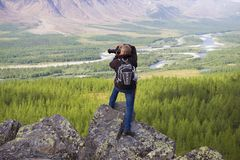 A photographer in the mountains of the Polar Urals photographs the Sob River valley. YAMAL, RUSSIA - AUGUST 20, 2018: A photographer in the mountains of the royalty free stock photo