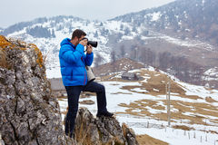 Photographer on the mountains. Tourist taking pictures to the mountains on winter time Stock Photography