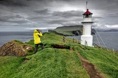 Photographer in mykinos faroe islands. Photographer with yellow raincoat take a picture of lighthouse in mykinos faroe islands stock photography