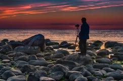 Photographer near baltic sea sunset. Travel in Latvia - Baltic sea sunset on rock beach Royalty Free Stock Image