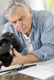 Photographer at office looking at shots on camera Royalty Free Stock Image