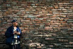 Photographer by the old bricks wall texture Royalty Free Stock Images
