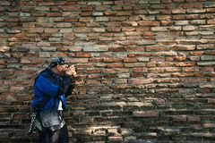 Photographer by the old bricks wall texture Stock Images