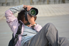 Photographer. Old women photographer taking pictures lying on the ground Royalty Free Stock Image