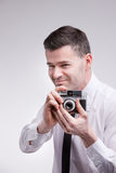 photographer with an oldstyle analogue photocamera shooting photographs with a sly smile royalty free stock photos