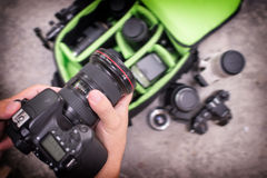 Photographer pack his camera and lenses to bagpack. Royalty Free Stock Photo