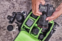 Photographer pack his camera and lenses to bagpack. Stock Photography