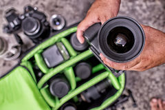 Photographer pack his camera and lenses to bagpack. Royalty Free Stock Photography