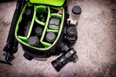 Photographer pack his camera and lenses to bagpack. Stock Images