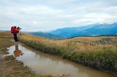 Photographer, paddle and autumn mountains Royalty Free Stock Photos