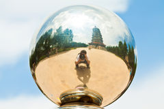 Photographer and pagoda in a metal ball Stock Images