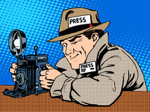 Photographer paparazzi at work press media camera. The reporter looks at pictures. Pop art retro style Royalty Free Stock Photography
