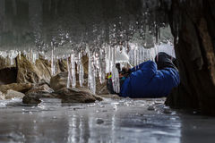 Photographer photographed in the grotto icicle. Stock Images