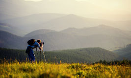 Photographer photographed mountains in summer, photographs fog Royalty Free Stock Image